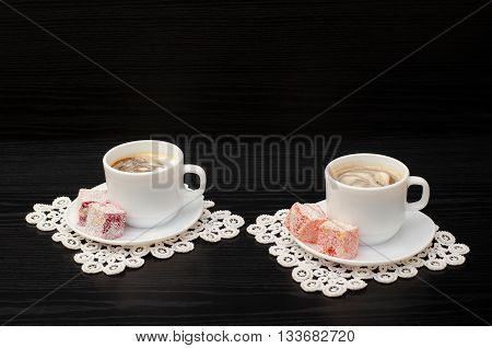 Side view of two mugs of coffee with ice-cream Turkish delight on a saucer on white lace napkins. Black background