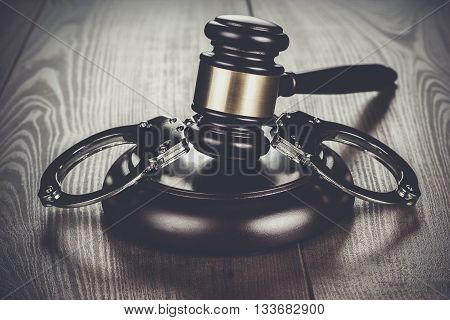 handcuffs and judge gavel on the brown wooden table