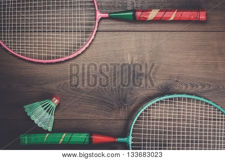 shuttlecock and badminton rackets on wooden background