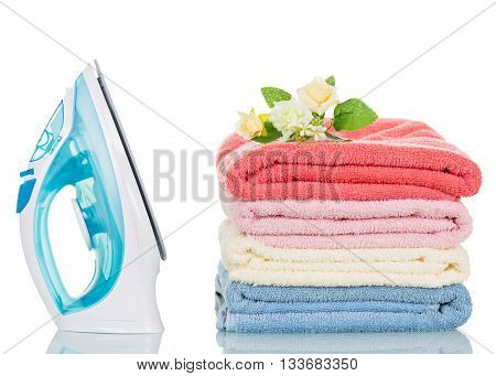 Steam iron and colorful towels isolated on a white background.