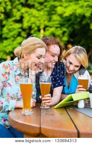 Woman showing friends touch pad in beer garden