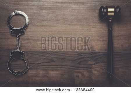 handcuffs and judge gavel on brown wooden background