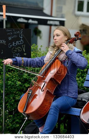VILNIUS LITHUANIA - MAY 16: Unidentified musician plays violoncello in Street music day on May 16 2015 in Vilnius. Its a most popular event on May in Vilnius Lithuania