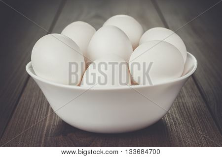 some eggs in white bowl on wooden table