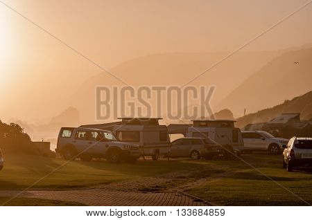 STORMS RIVER MOUTH SOUTH AFRICA - FEBRUARY 29 2016: An almost sepia scene as the sun is setting behind fog entering from the Indian Ocean into the Storms River Mouth Rest Camp