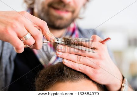 Barber trimming man hair in haircutter shop