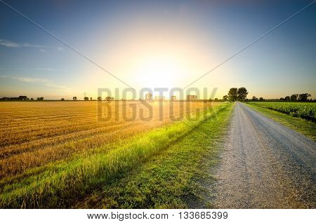 Long gravel road to sunset in the country