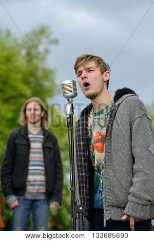 VILNIUS LITHUANIA - MAY 16: Unidentified young musician sings in Street Music Day on May 16 2015 in Vilnius. Its a most popular event on May in Vilnius Lithuania