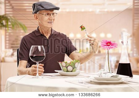 Discontent mature man sitting in a restaurant and looking at their food in disgust