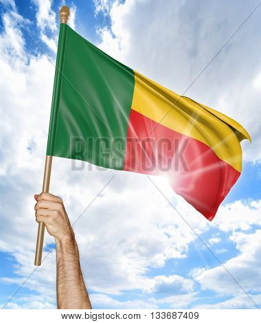 Person's hand holding the Benin national flag and waving it in the sky, part 3D rendering