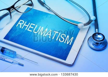 Stop rheumatism word on tablet screen with medical equipment on background.