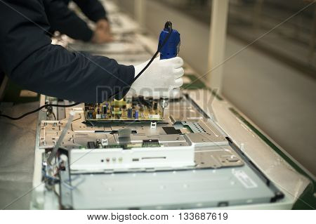 Electronic technician at work. Manual work in electronic industry. Production line.