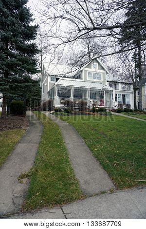 HARBOR SPRINGS, MICHIGAN / UNITED STATES - DECEMBER 24, 2015: A home with wraparound porch under the bluff on Fourth Street in Harbor Springs, during December.