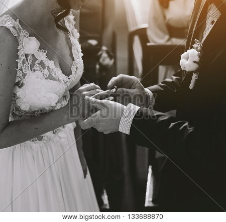 groom wears the ring on the finger of the bride in the church