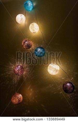 Electric garland lights with multi-colored balls of yarn muted colors.