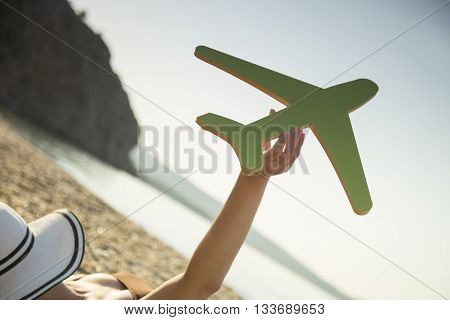 Female hand holding a cardboard airplane with the seascape in the background. Summer vacations transportation advertisement
