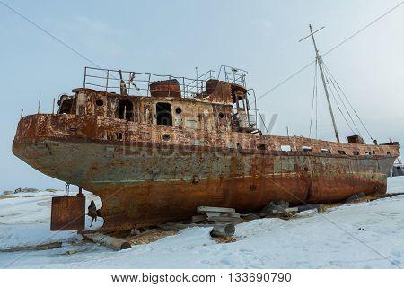 Old rusty ship on the winter shore of Lake Baikal.