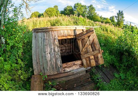 Wooden water well at the russian village in summer day