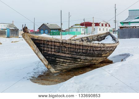 Ust-Barguzin, Russia - March 04, 2016: Wooden fishing boat on the winter snow-covered coast.
