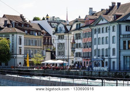 LUCERNE SWITZERLAND - MAY 08 2016: Historic buildings located along the river Reuss and many restaurants invites tourists to spend their free time surrounded by variety of sightseeing attractions