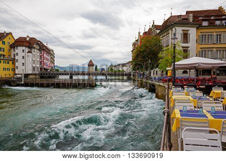 LUCERNE SWITZERLAND - MAY 11 2016: Cafes and the old buildings along the river Reuss flowing through the Old Town shows unique character of the city and variety of tourist attractions