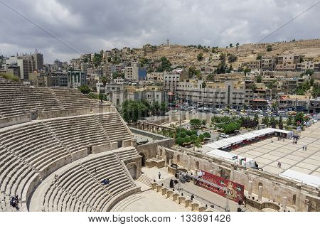 Amman, Jordan -May 28, 2016: Roman amphitheatre in downtown with Amman cityscape and citadel hill at background