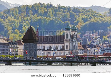 LUCERNE SWITZERLAND - MAY 04 2016: Early evening view towards the Jesuit Church located at the Reuss river bank and The World famous Watertower (Wasserturm) with its octagonal structure