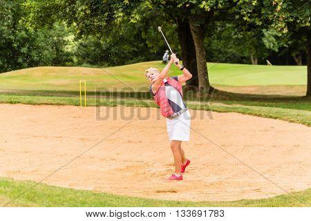Senior woman at golf having stroke in sand bunker