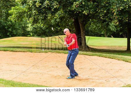 Senior man at golf having stroke in sand bunker