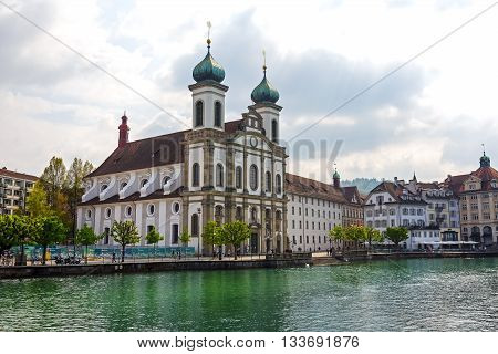 LUCERNE SWITZERLAND - MAY 02 2016: View towards the Jesuit Church located by the Reuss river in old town. It is widely believed to be the most beautiful Baroque church in Switzerland
