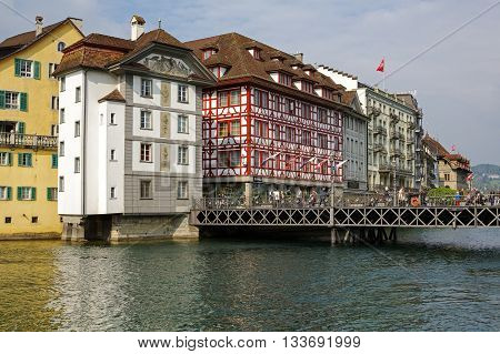 LUCERNE SWITZERLAND - MAY 02 2016: Old colorful buildings along the river shows unique character of Old Town and it looks to be tuned with modern times and offers variety of sightseeing attractions