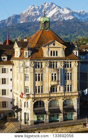 LUCERNE SWITZERLAND - MAY 05 2016: Nice building located on the banks of the river with visible above the top of Mount Pilatus presents the unique character of the city that offers many attractions