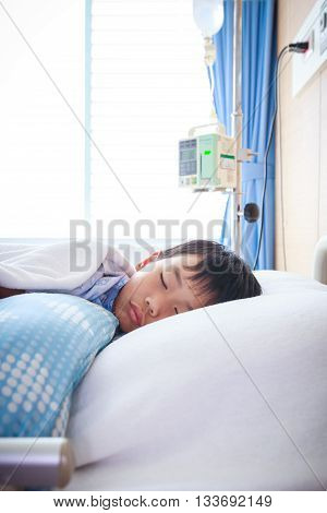 Illness asian boy sleeping at modern and comfortable equipped hospital room. Health care and people concept.