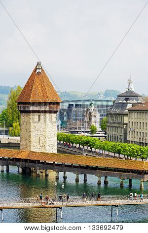 LUCERNE SWITZERLAND - MAY 02 2016: The octagonal tall tower (Wasserturm) together with the Chapel Bridge (Kapellbruecke) it is one of the Lucerne's most famous tourists attraction