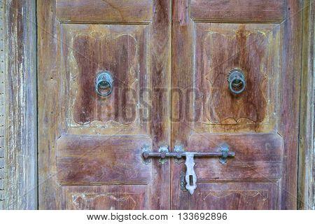 Rustic style wooden door with old fashioned door knobs
