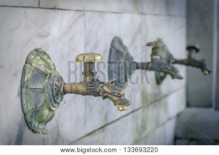 Old street washbasin with a few taps.