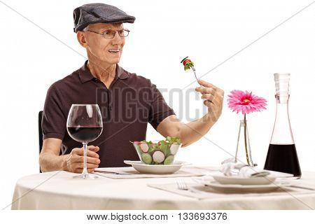 Displeased senior looking at a salad in disgust seated at a restaurant table isolated on white background