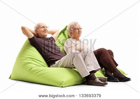 Relaxed elderly couple sitting on comfortable green beanbags isolated on white background