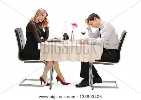 Young couple sitting at a table and arguing with each other isolated on white background