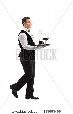 Full length profile shot of a young waiter carrying a tray with wine and two glasses isolated on white background
