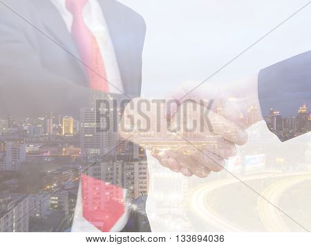Double exposure of handshake of two smart business mans waring black suit on modern building in nightlife cityscape