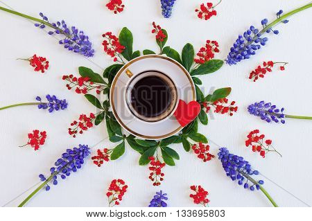 A cup of coffee in a flower wreath. Coffee and good mood. Cup of coffee and red heart in a flower arrangement. The top view.