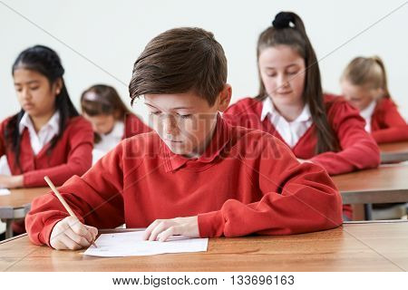 Male Pupil At Desk Taking School Exam