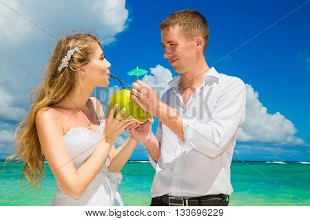 Happy bride and groom drink coconut water and having fun on a tropical beach. Wedding and honeymoon on the tropical island.