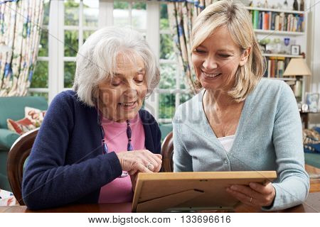 Senior Woman Looks At Photo Frame With Mature Female Neighbor
