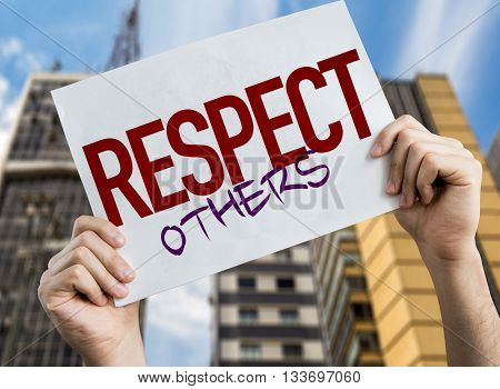 Respect Others placard with cityscape on background