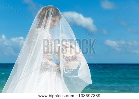 Beautiful brunette fiancee in white wedding dress with big long white train and with wedding bouquet stand on shore sea near the wedding arch of vines and flowers. Wedding and honeymoon concept.