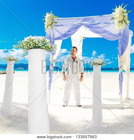 Wedding ceremony on a tropical beach in blue.The groom waits for the bride under the arch decorated with flowers on the sandy beach.