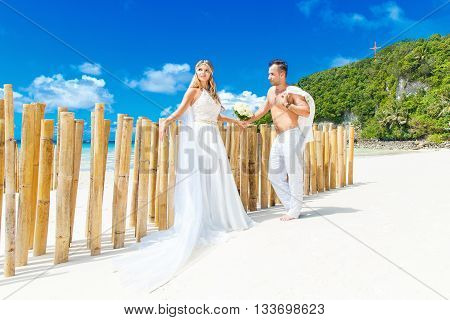Beautiful blond bride in white wedding dress with big long white veil and groom having fun on shore sea. Tropical sea in the background. Summer vacation concept.
