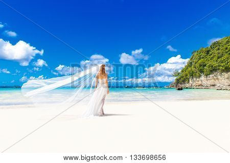 Beautiful blond bride in white wedding dress with big long white veil and with wedding bouquet stand on shore sea. Tropical sea in the background. Summer vacation concept.
